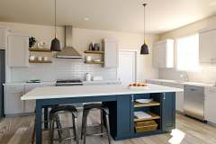 Bright kitchen with blue island and pendants.