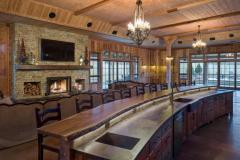 Side view of the bar adorned with a natural wood countertop. It is long and curved almost as if the tree the wood came from was grown especially for this space.
