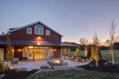 The exterior of the red party barn in the evening. A stone accent wall surrounds a fire pit and provides plenty of seating.