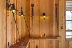 Wood shelves supported by chains are attached to the untreated wood walls.