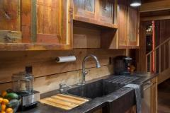 A view of the rustic kitchen in the party barn with wood cabinetry, a black countertop and a backsplash made from horizontal planks of untreated wood.