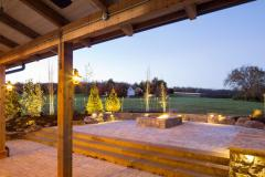 The exterior of the red party barn's covered patio in the evening. A stone accent wall surrounds a fire pit and provides plenty of seating.