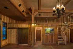 The entryway of the Party Barn has wrought-iron candlelight chandeliers and lantern-like sconces add to the rustic feel of the space.