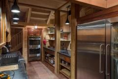 A view of the rustic kitchen in the party barn with wood cabinetry, open shelving, and an industrial size stainless steel refrigerator.