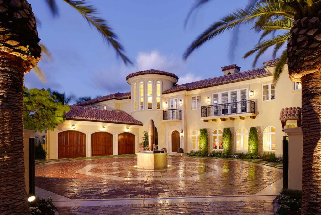 Spanish style home design with a three car garage and turret.