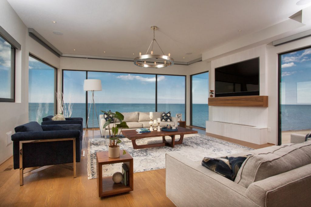 Bright living room with floor to ceiling windows exposing the ocean view.