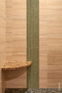 Green glass tile is inlayed vertically against neutral field tile to harken to bamboo poles in a curbless shower designed by Robin Rigby Fisher