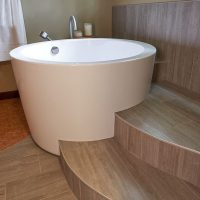 A japanese soaking tub is an anchor piece in this large primary bathroom design by Robin Rigby Fisher