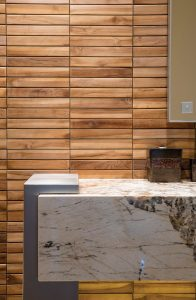 Warm colored teak wall tile and cool stainless steel of a vanity base are brought together with lively natural stone.