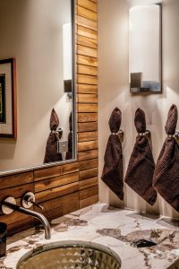 Teak covered walls, custom mirror, and interesting towel rings give the simple bathroom and sophisticated feeling.