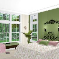 Green and white bedroom with a window seat and large windows.