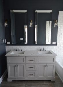 This white vanity and subway tile stand up to the deep blue walls in Danielle Burgers bathroom design.