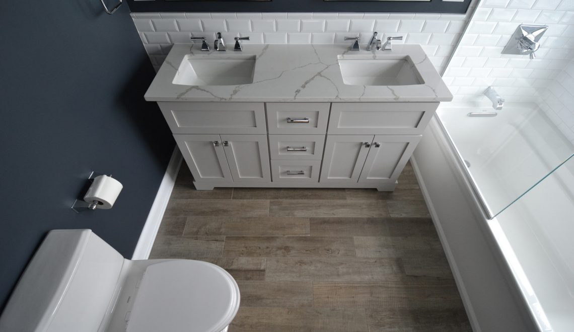 Double sink with blue wall, oak floor, and white backsplash