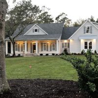 Traditional home design with white siding, a large front porch, and an attached garage.