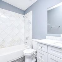 Guest bathroom with tub shower and white vanity.