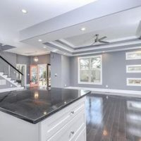 Open concept kitchen design with custom, vaulted ceiling, hardwood floors and a large island.