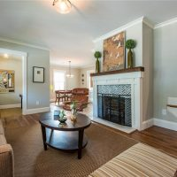 Family room with large fireplace and mantel, hardwood floors, light blue paint.