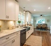 Traditional white kitchen with marble counter top and hardwood floors.