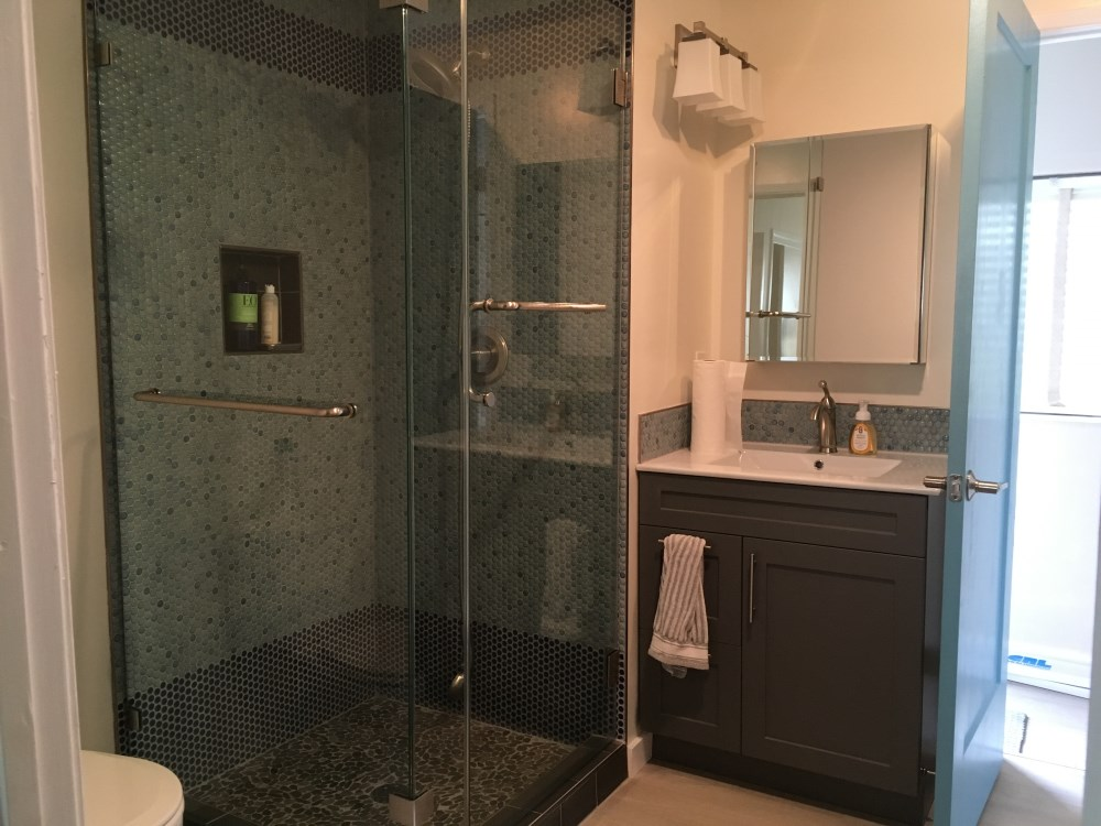 Remodeled bathroom with glass shower and vanity.