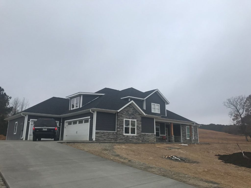 Real photo of completed project with multi-car garage and stone accents.