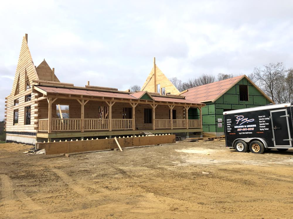 Log home under construction with front porch complete.