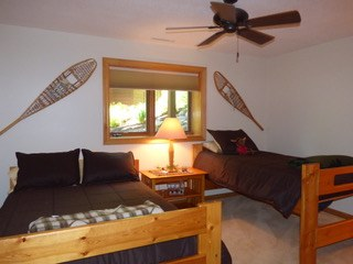 Bedroom with two twin beds and old fashion snowshoes as decoration.