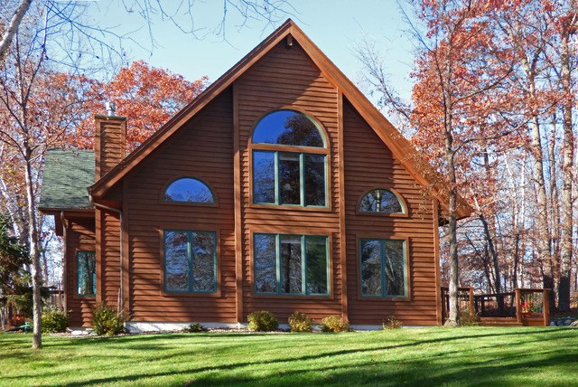 Exterior view of a one and a half story log home.