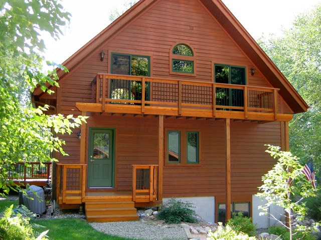 Exterior view of a one and a half story log home with a balcony.
