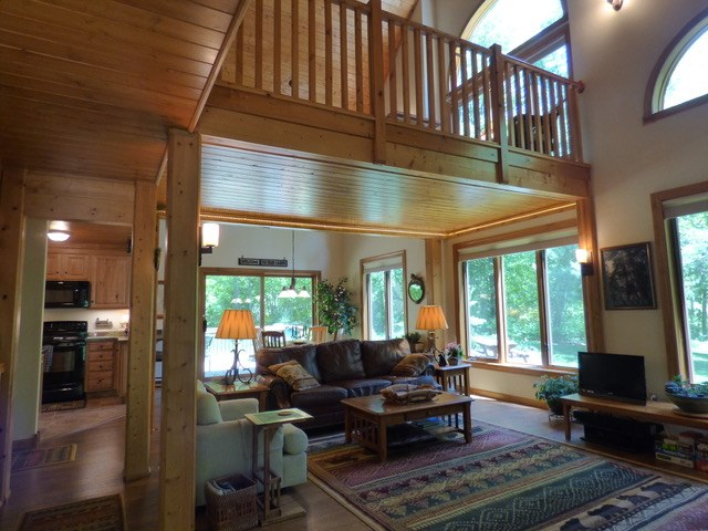 Log home living room with vaulted ceilings and loft.