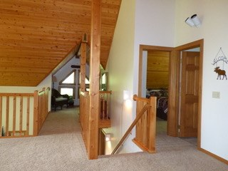 Upstairs of a log home with vaulted ceilings.