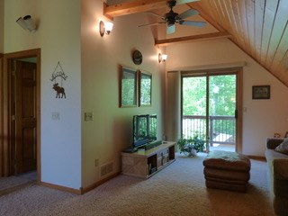 Family area with high ceilings, exposed beams and sliding glass door leading to the balcony.