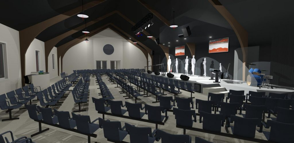 Interior of a church with vaulted ceilings, stadium seating and stage.