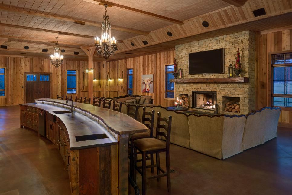 Spacious high end rustic feeling living room with stone fireplace and woodwork.