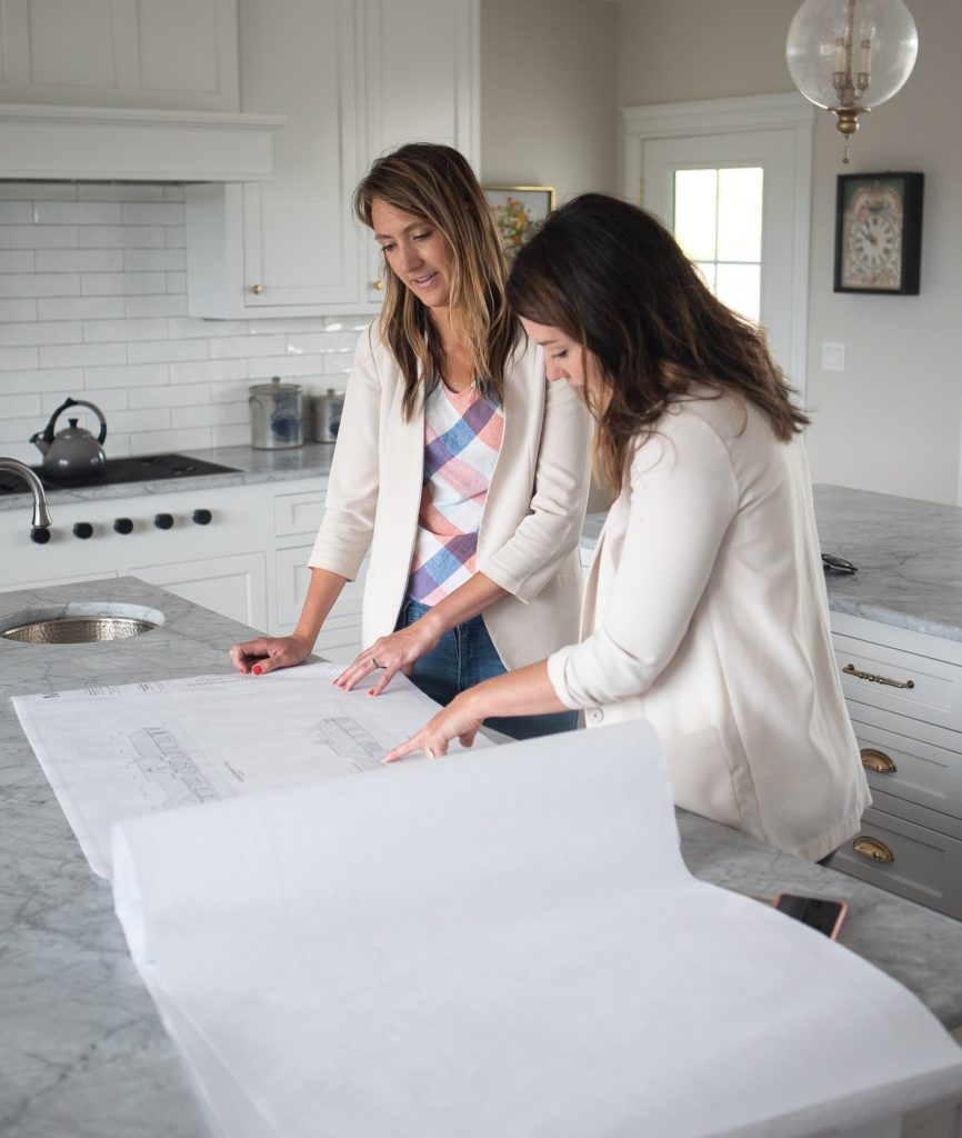 Two sisters read over construction documents in kitchen.