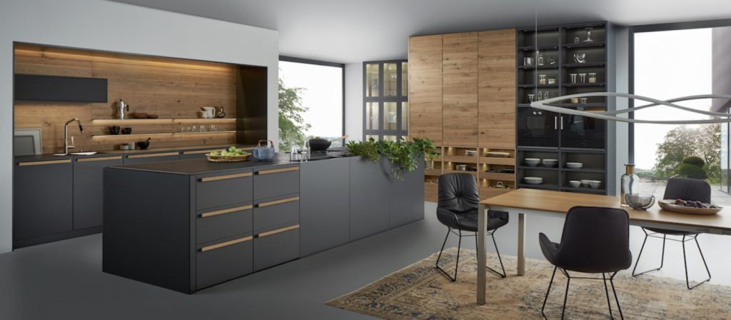 A modern kitchen with black cabinets and natural accents designed by Leicht.