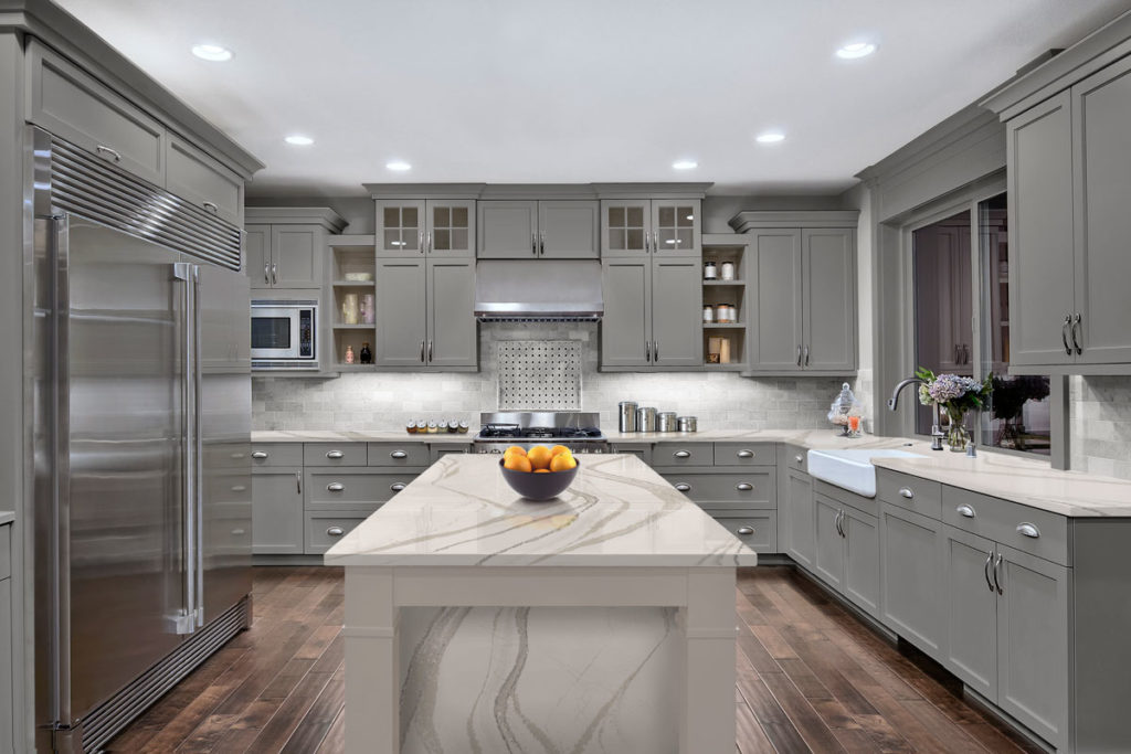 Large kitchen with marble counter top and grey cabinets.