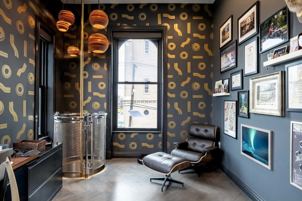 Dark office with black and gold features and leather furniture.