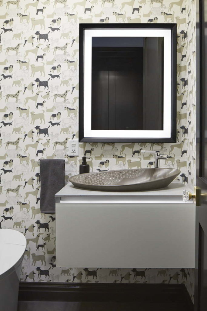 Powder room with dog wall paper and stone bowl sink.