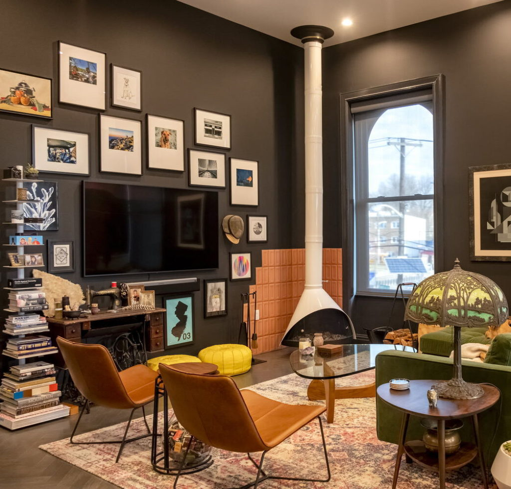 Image of a living room with black walls, a custom fireplace and a gallery wall.