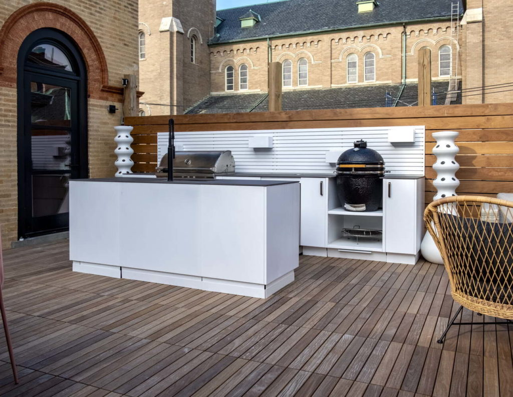 Roof top kitchen with white cabinets, natural brick walls and wood flooring.