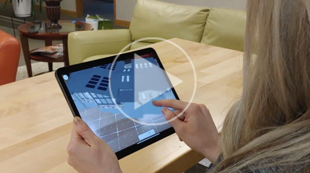 Person holding tablet using the 3D viewer app to navigate the house design in 3D.