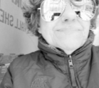 Black and white image of a woman with short hair and large sunglasses.