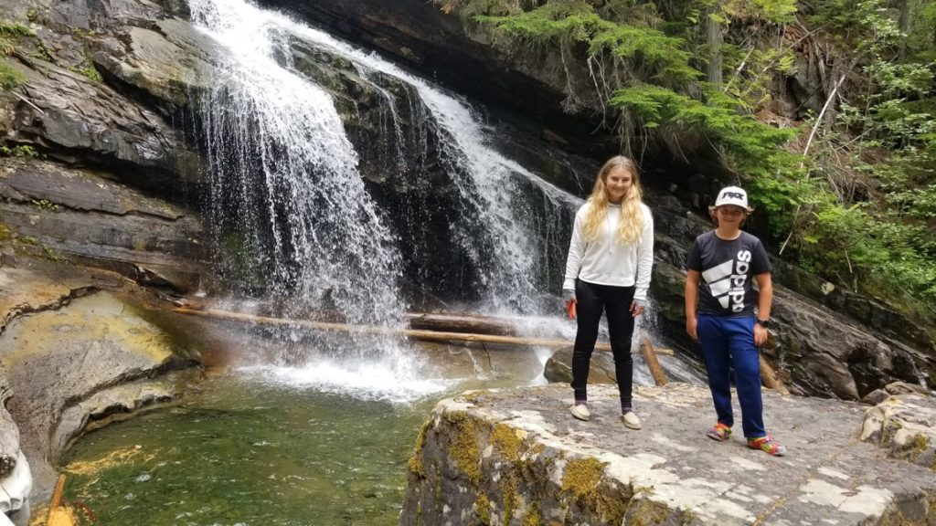 Kids posing in front of a waterfall they discovered while camping.