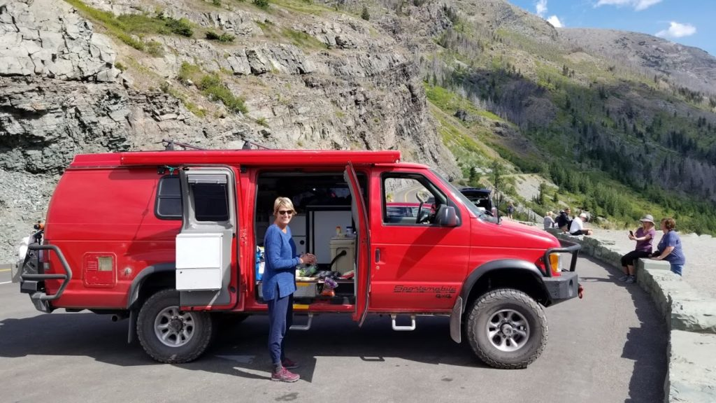A woman standing with a 2001 Ford E350 extended body Sportsmobile with penthouse pop-top and a Quigley 4X4 conversion.